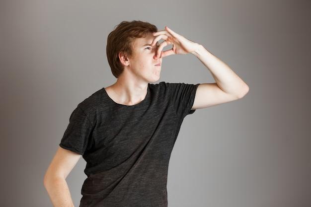 Молодой рыжий мужчина запах неприятный, отрицательный. по серой стене. скопируйте пространство.