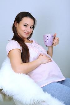 안락의 자에 앉아 표면 표면에 컵을 들고 젊은 우세한 여자