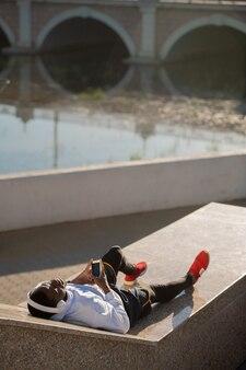 야외 훈련 후 강변에 누워 음악과 함께 휴식을 즐기는 스포츠웨어와 흰색 헤드폰에서 젊은 편안한 아프리카 남자