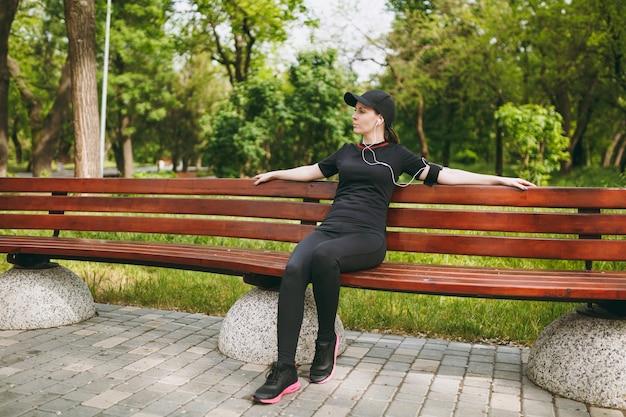 屋外の都市公園のベンチで音楽を聴いてトレーニングトレーニングの後に休んでいるイヤフォンと黒いユニフォームとキャップの若いリラックスした運動のかなりブルネットの女性