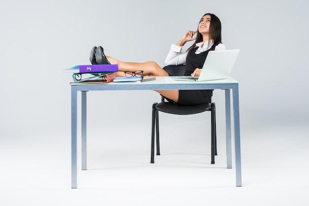 作業テーブルに足を持つ若いリラックスしたビジネス女性は灰色で隔離の仕事の終わりをお楽しみ