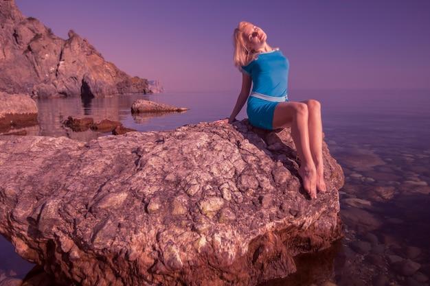 젊은 편안한 백인 여자는 돌에 앉아 여름 태양 광선을 즐긴다