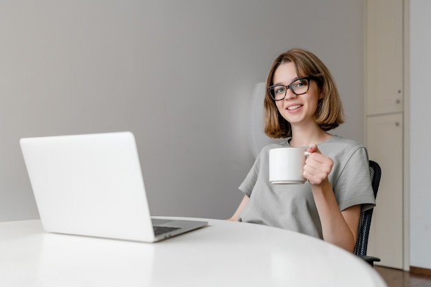 Young relaxed caucasian woman smiling sitting with laptop in the apartment with cup in her hands