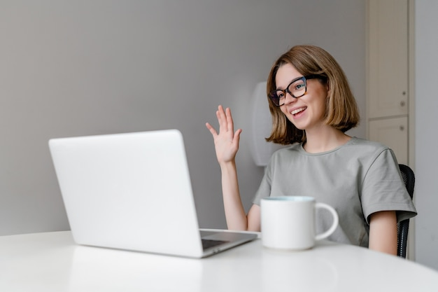 Young relaxed caucasian woman smiling waving with laptop in the apartment with cup on the table