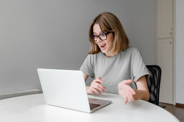 Young relaxed caucasian woman speaking sitting with laptop in the apartment