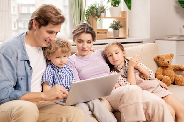 Молодая расслабленная семья в повседневной одежде смотрит фильм на дисплее ноутбука, сидя