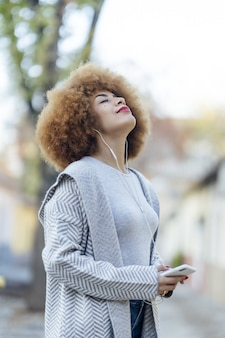 公園でヘッドフォンで音楽を聴いている巻き毛の若いリラックスしたヒスパニック系女性