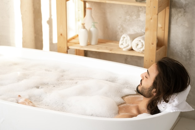 Young relaxed man enjoying bath with foam while putting his head on soft rolled white towel