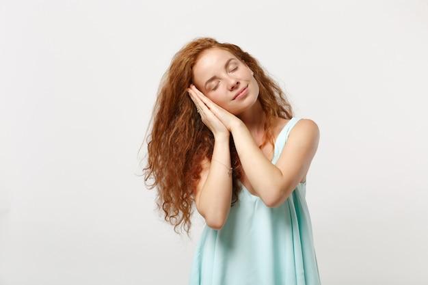 スタジオで白い背景に分離されたポーズでカジュアルな明るい服を着た若いリラックスした赤毛の女性。人々の誠実な感情のライフスタイルの概念。コピースペースをモックアップします。手を組んで頬の下で寝ます。