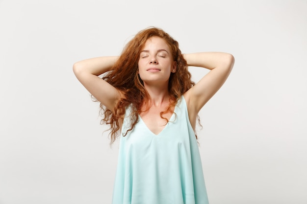 スタジオの白い壁の背景に分離されたポーズでカジュアルな明るい服を着た若いリラックスした赤毛の女性。人々の誠実な感情のライフスタイルの概念。コピースペースをモックアップします。彼女の頭の後ろに手を置いて寝なさい。