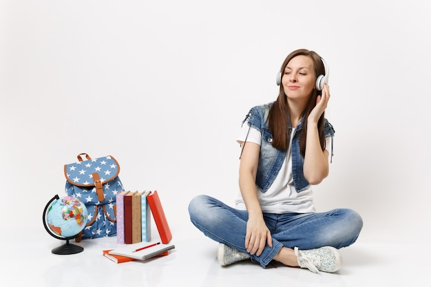 Young relaxed tender woman student with closed eyes in headphones listening music sitting near globe, backpack, school books isolated on white wall