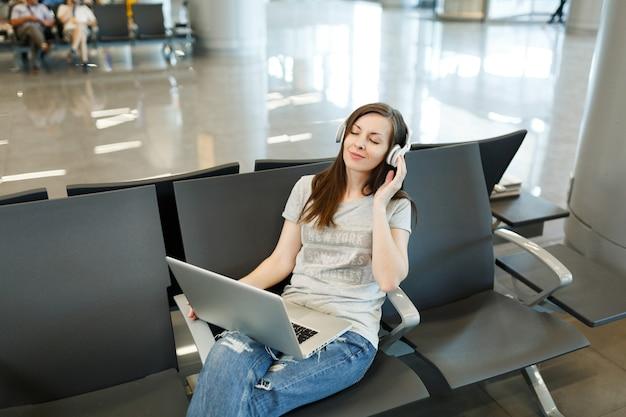 Молодая расслабленная туристическая женщина путешественника с наушниками, слушающая музыку, работающая на ноутбуке, ждет в холле вестибюля в международном аэропорту