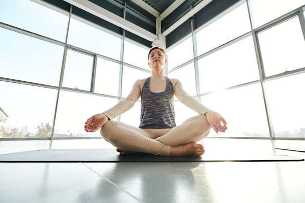 Young relaxed woman in activewear sitting in pose of lotus with crossed legs while exercising on mat in large gym