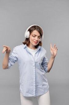 Молодая расслабленная женщина в повседневной одежде и наушниках, наслаждаясь музыкой во время танцев в изоляции