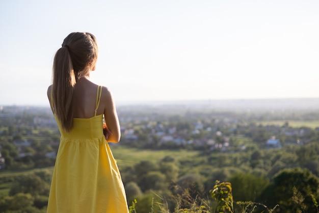 Молодая расслабленная женщина, стоящая в зеленом поле, глядя на закат в вечерней природе. концепция релаксации и медитации.