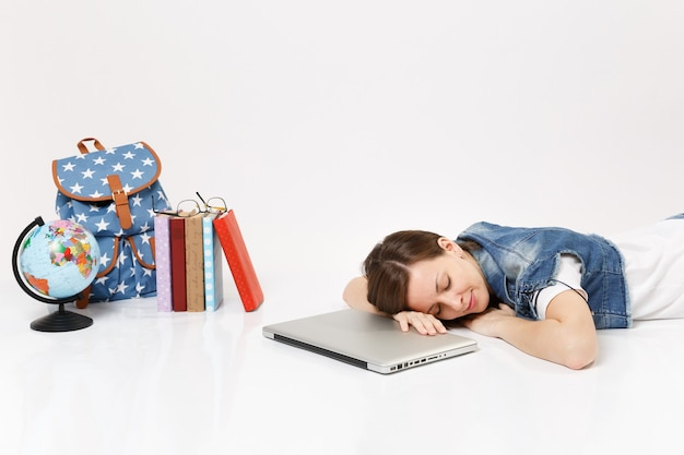 Young relaxed woman student in denim clothes sleeping on laptop pc computer lying near globe, backpack, school books