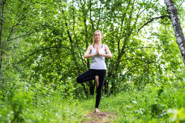 A young relaxed woman with closed eyes is standing on a forest, her arms are folded over her chest and in a yoga tree pose