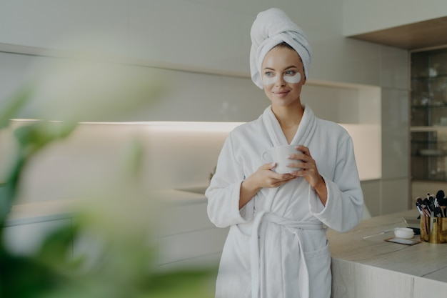 Young relaxed woman with cosmetic patches under eyes in bathrobe and hair wrapped in towel holding cup of tea and resting after spa treatments or taking bath while standing in modern kitchen at home