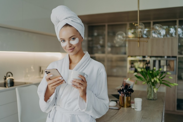 Young relaxed woman with cosmetic patches under eyes using smartphone and smiling, female in bathrobe and hair wrapped in towel drinking tea while resting after taking bath at home