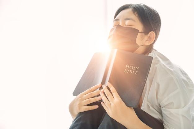 保護マスクを着用し、自宅で助けを求めて神に祈る若い宗教的な女性。医療用フェイスマスクの女の子のキリスト教の祈り。コロナウイルスcovid-19