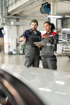 디지털 태블릿의 데이터를 사용하면서 작업장에서 제복을 입은 젊은 수리공과 그의 여성 동료