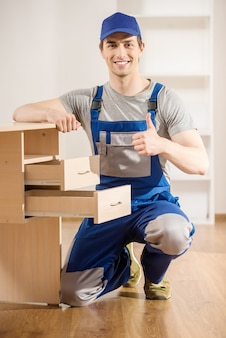 Young repairman assembling new table at home interior.