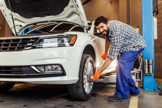 車のタイヤを固定し、前に微笑んでいる若い修理工