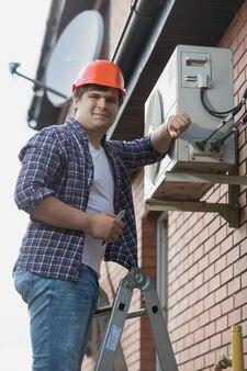 외벽에 에어컨을 설치하는 젊은 수리공
