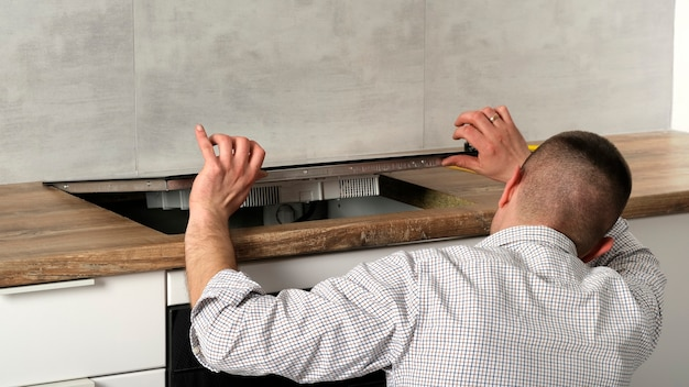 A young repairman installs a black induction hob in a modern white scandinavian style kitchen with a concrete wall. electrician man, do it yourself. household chores.