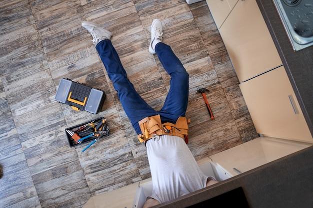 악기 옆 바닥에 누워 있는 젊은 수리공
