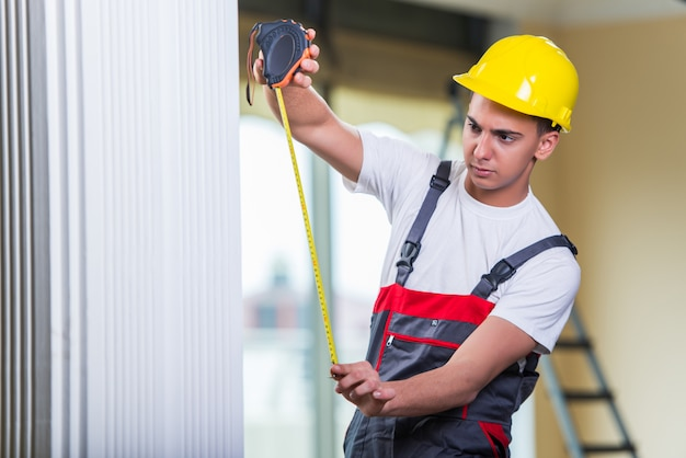 Young repairman with tape measure working on repairs