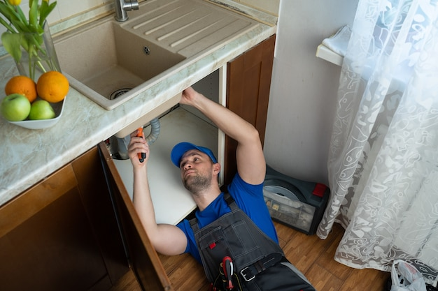 Young repairman with tools in his hands and a blue cap is fixing the sink in the kitchen