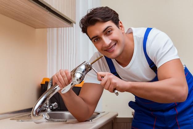 キッチンで働く若い修理工