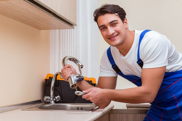 Young repairman working at the kitchen