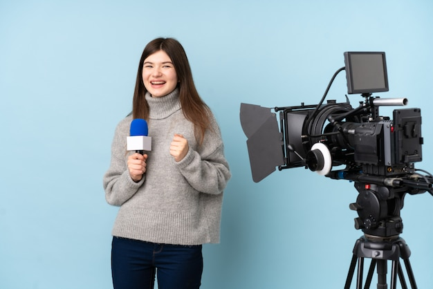 Young reporter woman holding a microphone and reporting news celebrating a victory
