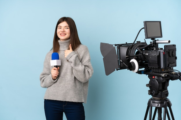 Young reporter woman holding a microphone and reporting news giving a thumbs up gesture