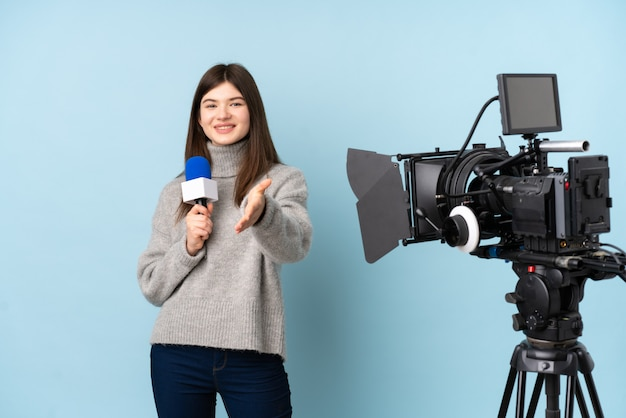 Young reporter woman holding a microphone and reporting news handshaking after good deal