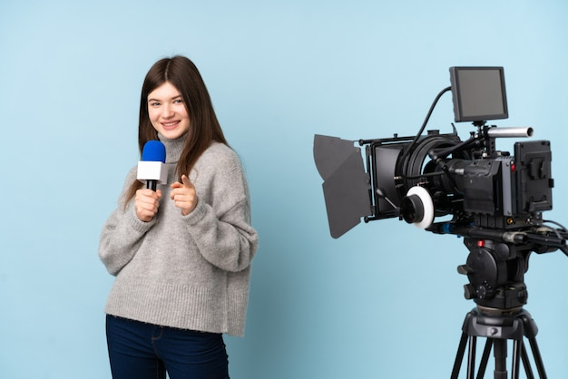 Young reporter woman holding a microphone and reporting news points finger at you