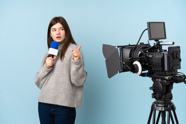 Young reporter woman holding a microphone and reporting news surprised and pointing finger to the side