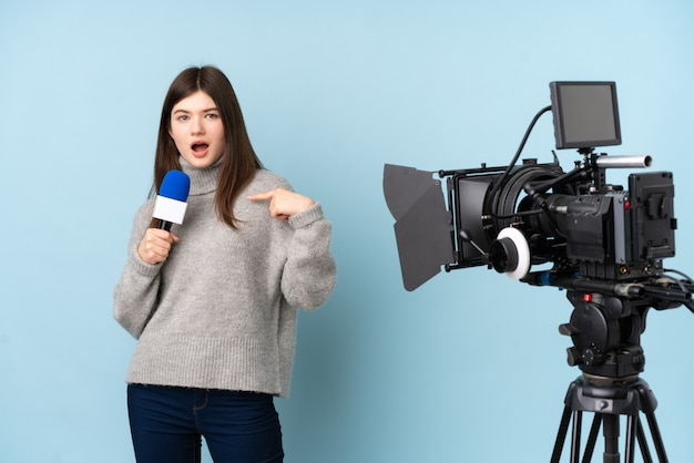 Young reporter woman holding a microphone and reporting news with surprise facial expression