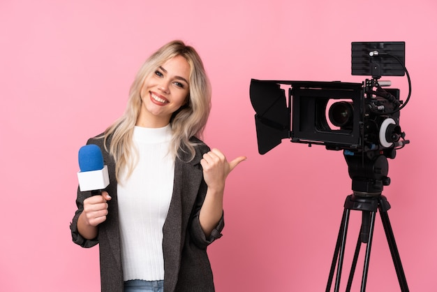 Young reporter woman over isolated wall