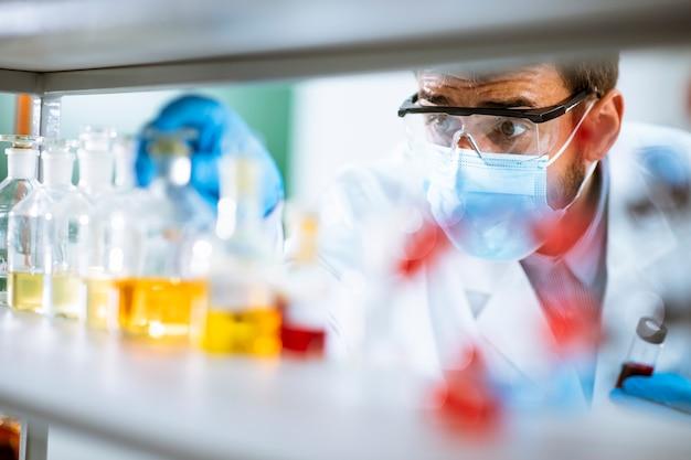 研究室で試験管をチェック保護ゴーグルを持つ若い研究者