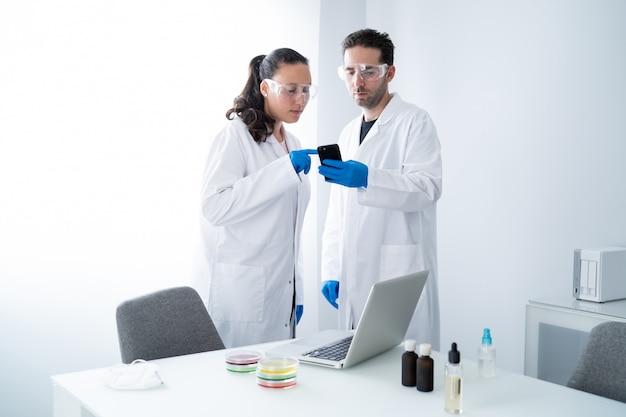 Молодые исследователи просматривают информацию на смартфоне о своей исследовательской работе в растворе петри в лаборатории
