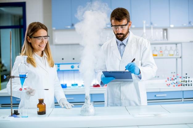화학 실험실 테이블에서 연기 실험을하는 젊은 연구원