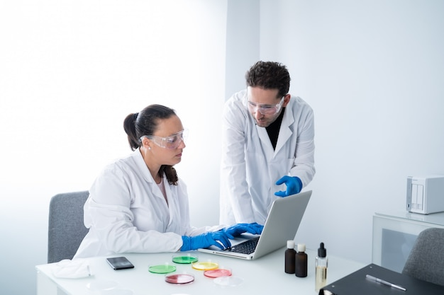 Young researchers examining solution in petri dish at a laboratory