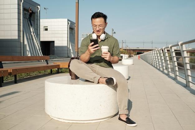 음료를 마시고 스마트폰으로 비디오를 보는 젊은 편안한 사업가