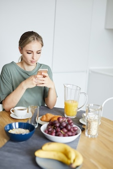Молодая спокойная женщина, смотрящая видео в смартфоне поданным столом