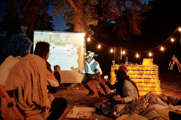 Молодые спокойные друзья пьют пиво с закусками во время просмотра трансляции футбольного матча на большом белом экране вечером в естественной среде