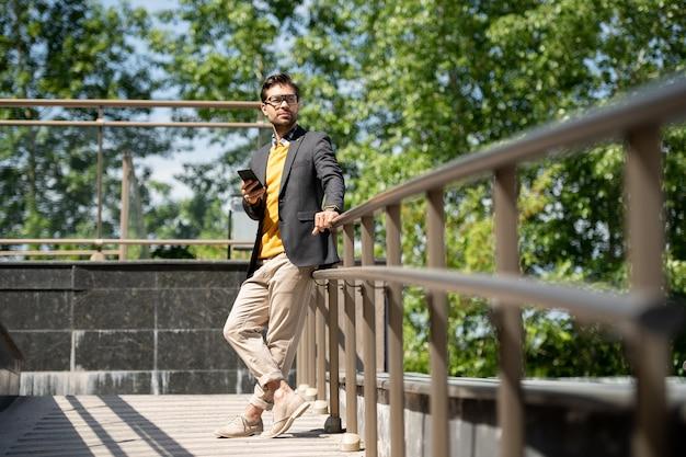夏の日に現代的な建物からさほど遠くない手すりのそばに立っている間スマートフォンを使用してスマートカジュアルの落ち着いた若者