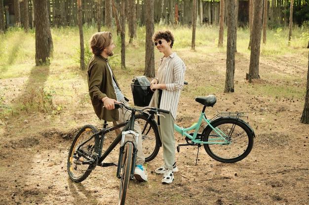 サングラスをかけた幸せな妻と話し、松の木の幹の間で自転車のそばに立っている間、彼女を見ている若い安らかな男